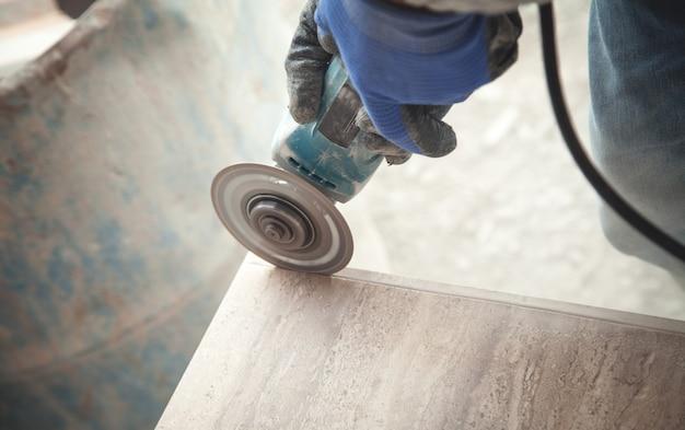 Travailleur coupant un carreau avec un broyeur.