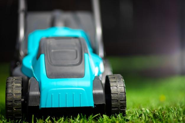 Travailleur coupant l'herbe dans une cour verte. un homme avec une tondeuse à gazon électrique tondant une pelouse