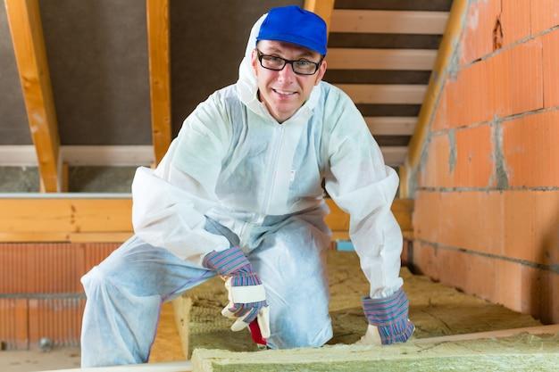 Travailleur coupant un matériau isolant