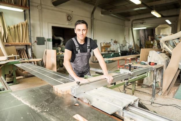 Travailleur coupant sur une scie circulaire à format dans une usine. coup moyen.