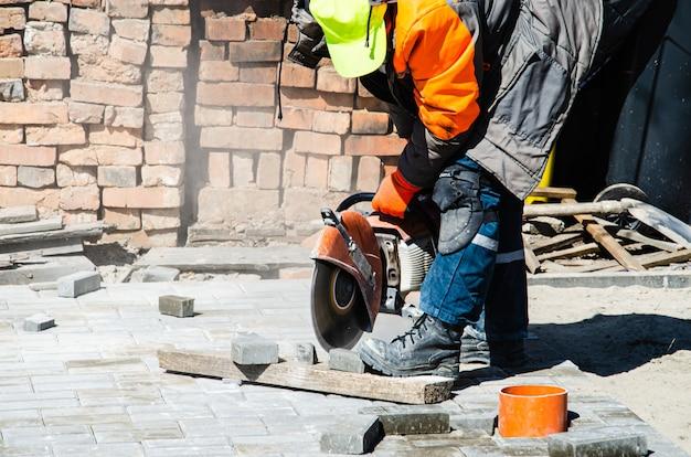 Un travailleur coupe des dalles de pavage avec un coupe-gaz et une scie à main