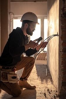 Le travailleur coupe des fils avec des pinces de monteurs de lignes