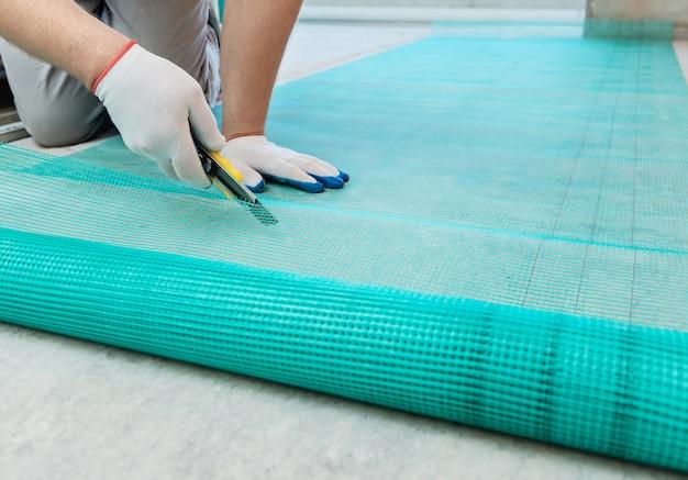 Un travailleur coupe une maille en fibre de verre.