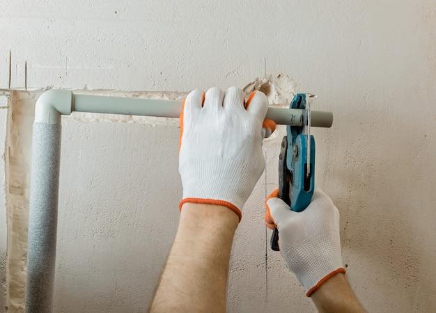 Un travailleur coupe la partie du tuyau avec des ciseaux à tuyau