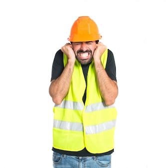 Travailleur couvrant ses oreilles sur fond blanc