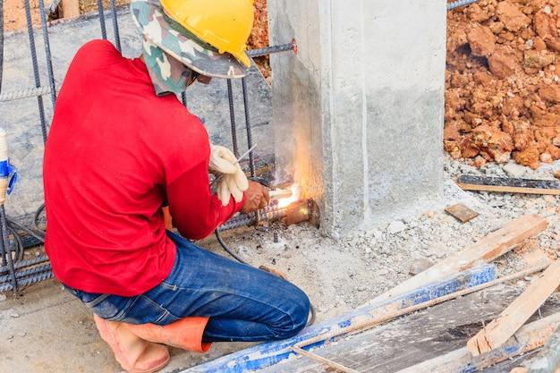 Travailleur dans des lunettes de protection soudant des tiges métalliques pour renforcer le béton sur le chantier de construction