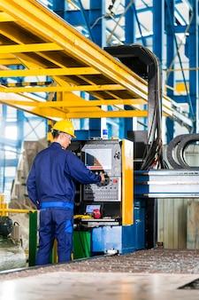 Travailleur dans l'usine de fabrication au panneau de commande de la machine cnc