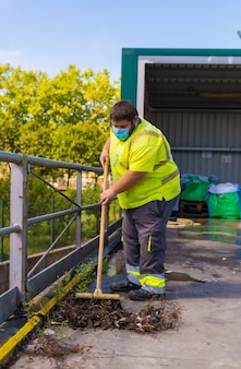 Travailleur dans une usine de recyclage ou point propre et ordures avec un masque facial et avec des protections de sécurité. balayer l'intérieur de l'enceinte