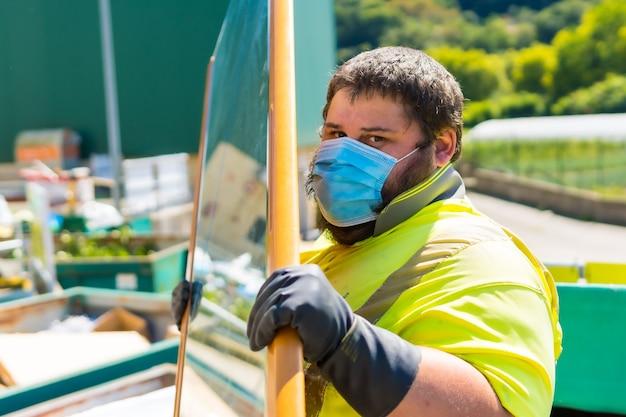 Travailleur dans une usine de recyclage ou point propre et ordures avec un masque facial et avec des protections de sécurité. nettoyage par l'opérateur et commande de l'installation
