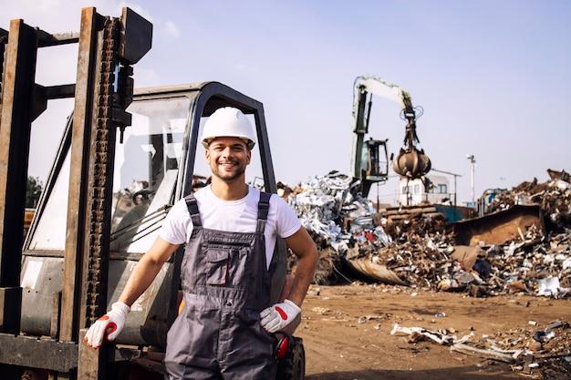 Travailleur debout par chariot élévateur tandis que la machine industrielle travaille avec des pièces de ferraille dans un parc à ferrailles