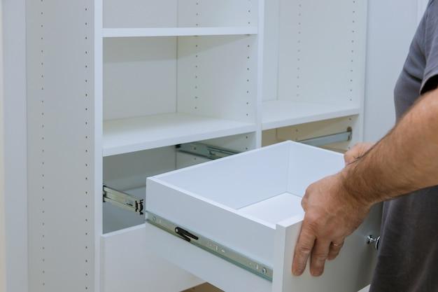 Le travailleur définit l'installation de la boîte le tiroir pour l'armoire de placard