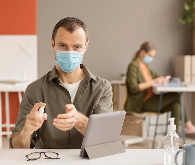 Travailleur désinfectant les mains au bureau