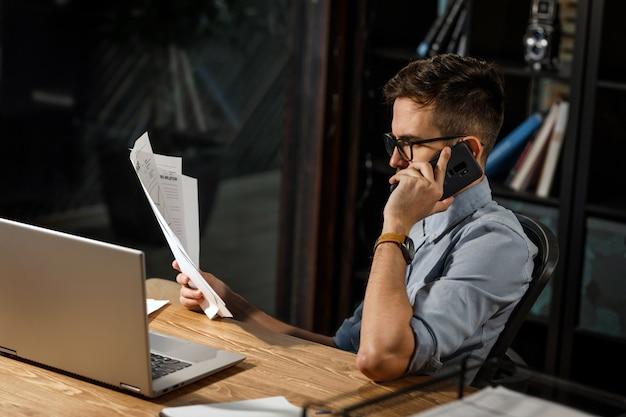 Travailleur diligent avec papiers s'exprimant au téléphone