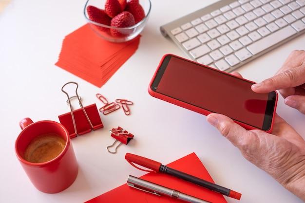 Le travailleur à domicile fait une pause avec du café et des fraises, en utilisant un téléphone avec écran rouge. bureau blanc et accessoires rouges
