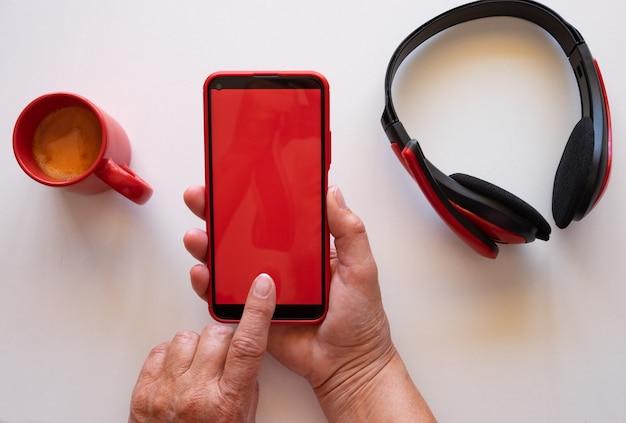 Le travailleur à domicile fait une pause avec une tasse de café, en utilisant un téléphone avec un écran rouge. casque de bureau blanc et rouge
