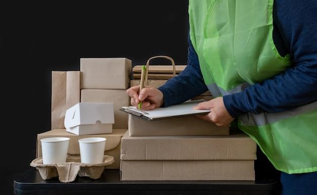 Le travailleur du service de livraison reste près du lieu de travail avec des boîtes et écrit sur tablette.