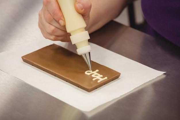 Travailleur écrit joyeux anniversaire avec poche à douille sur plaque de chocolat