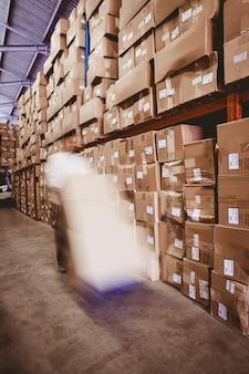 Travailleur avec empileur de fourche palette camion dans l'entrepôt