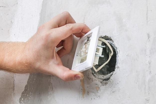 Un travailleur enlève l'interrupteur d'éclairage pour le papier peint.