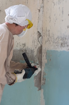 Le travailleur enlève la vieille peinture d'un mur en béton avec un marteau rotatif avec un ciseau, une méthode mécanique pour enlever la peinture, des travaux de réparation dans un appartement