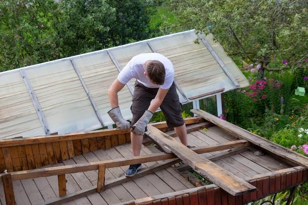 Le travailleur enlève les vieilles planches du toit, la maison est en cours de rénovation.