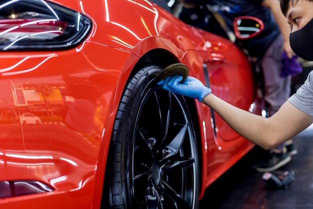 Travailleur d'entretien automobile polissage des roues de voiture avec un chiffon en microfibre.