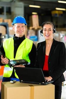 Travailleur d'équipe, conducteur d'entrepôt ou conducteur de chariot élévateur et superviseur de sexe féminin avec ordinateur portable, casque et téléphone portable, dans l'entrepôt de la société d'expédition de fret