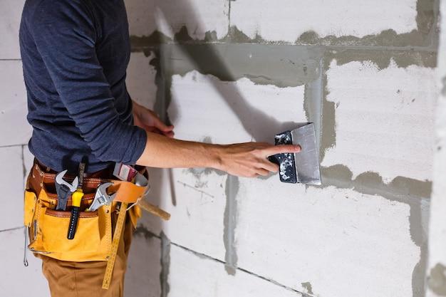 Le travailleur essuie les coutures à l'extérieur de la maison en brique. le constructeur traite la maçonnerie. maçon ouvrier maçon de construction installant une brique rouge avec un couteau à mastic à la truelle à l'extérieur.