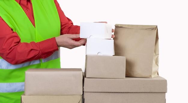 Le travailleur est dans un gilet vert tenant beaucoup de boîtes en papier, concept de livraison.