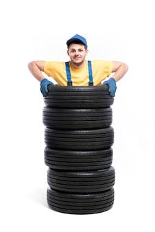 Travailleur est debout à l'intérieur d'un tas de pneus