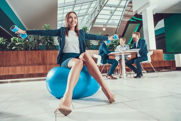 Travailleur exerce sur ballon de fitness au bureau.