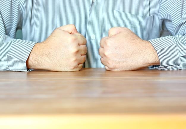 Le travailleur faisant une double poignée sur une table devant sa poitrine