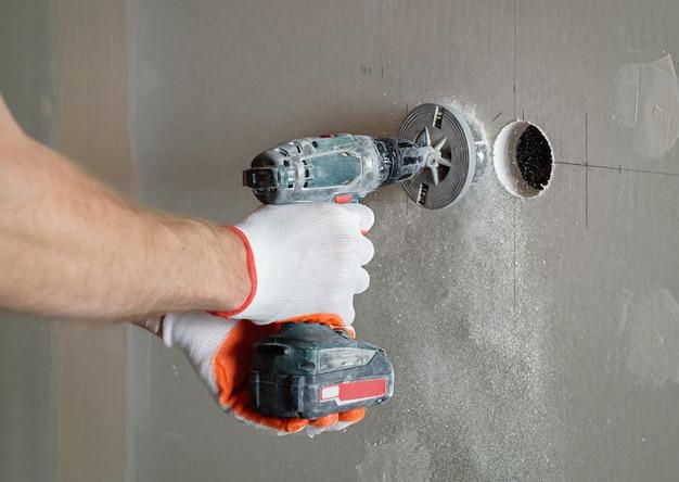 Travailleur faisant des trous dans la cloison sèche pour installer la prise à l'avenir