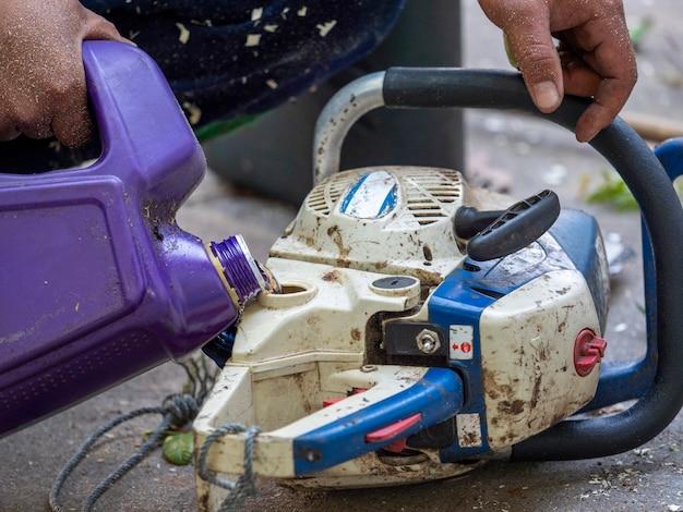 Le travailleur fait le plein de carburant à la tronçonneuse après le travail