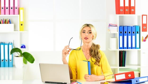 Travailleur. femme chef d'entreprise. femme assise à son bureau au bureau. femme d'affaires travaillant au bureau avec des documents. designer professionnel sur le lieu de travail au bureau. réceptionniste travaille à la réception.