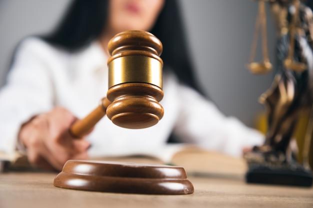 Travailleur femme tenant le marteau du juge. cabinet d'avocats