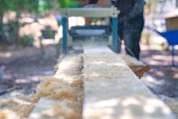 Le travailleur frotte la grande plaque de bois longue avec une machine à polir dans le jardin.