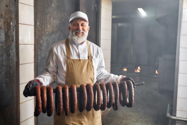 Travailleur de fumoir tenant des saucisses fumées, posant.