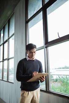 Travailleur homme asiatique debout écrire sur un presse-papiers