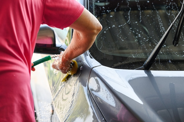 Travailleur homme lavant et frottant la voiture avec une éponge et de l'eau