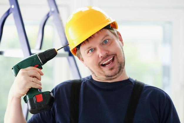 Travailleur idiot à l'aide de portrait de perceuse électrique