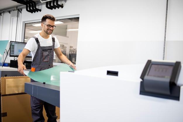 Un travailleur d'impression souriant utilise un ordinateur pour plaquer une machine dans une imprimerie.