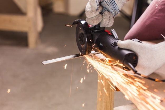 Travailleur de l'industrie lourde coupant de l'acier avec une meuleuse d'angle au service automobile
