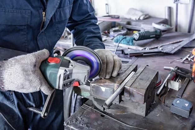Travailleur de l'industrie lourde coupe l'acier avec meuleuse d'angle au service de voiture
