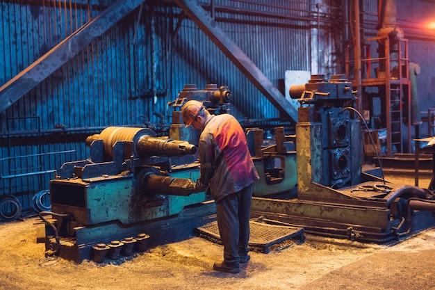 Travailleur de l'industrie lourde travaillant dur sur la machine. environnement industriel difficile.