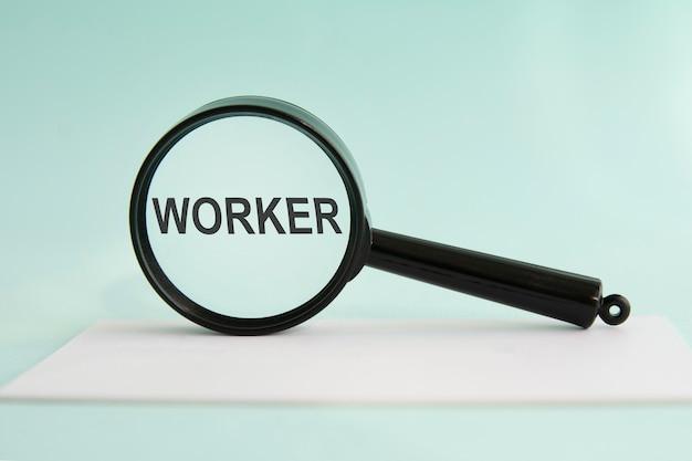 Travailleur d'inscription sur loupe, fond bleu, concept d'entreprise