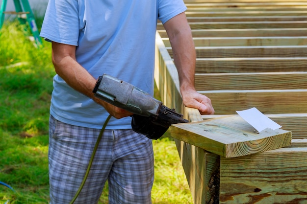 Travailleur installant un plancher de bois pour patio