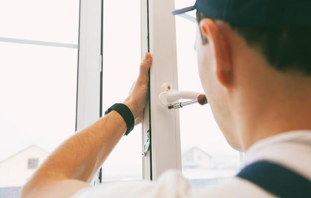 Le travailleur installant et vérifiant la fenêtre dans la maison
