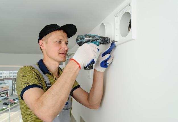 Un travailleur installe une grille de ventilation