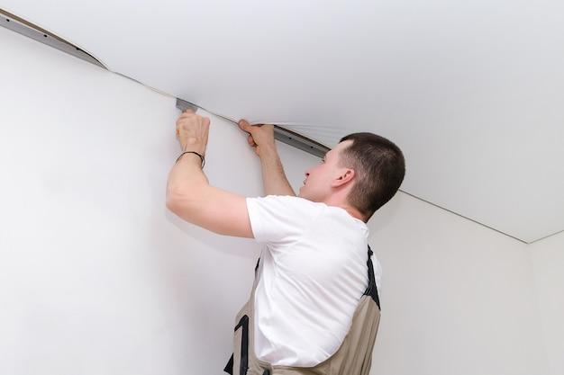 Travailleur installe un plafond tendu. concept de construction et de rénovation